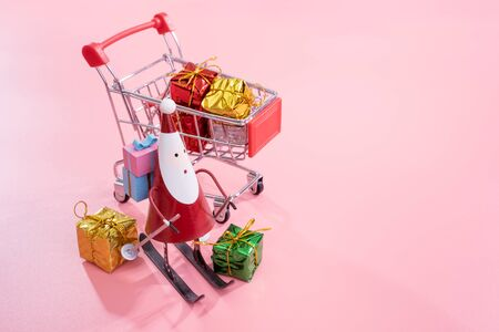 Christmas shopping concept, mini red shop cart trolley with Santa Claus toy and gift box isolated on pale pink background, blank copy space, close up