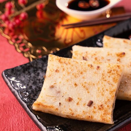 Chinese lunar new year food concept, Delicious turnip radish cake, local cuisine in restaurant with soy sauce on red background, close up, copy space Фото со стока