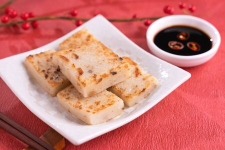Chinese lunar new year food concept, Delicious turnip radish cake, local cuisine in restaurant with soy sauce on red background, close up, copy space