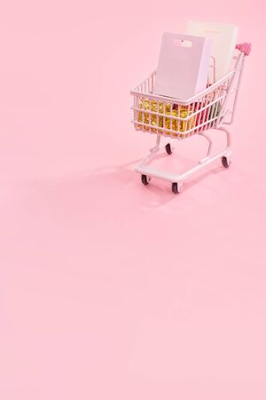 Annual sale shopping season concept - mini red shop cart trolley full of paper bag gift isolated on pale pink background, blank copy space, close up
