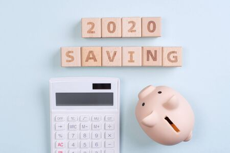 Abstract 2020 financial goal design concept - geometric wood blocks cubes on blue table background with piggy bank, top view, flat lay, copy space.