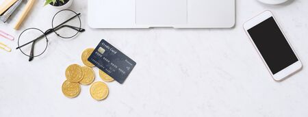 Concept of online payment with credit card with smart phone, laptop computer on office desk on clean bright marble table background, top view, flat lay Imagens