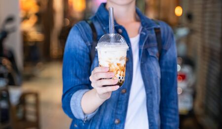 Young woman is holding, drinking brown sugar flavored tapioca pearl bubble milk tea with glass straw in night market of Taiwan, close up, bokeh