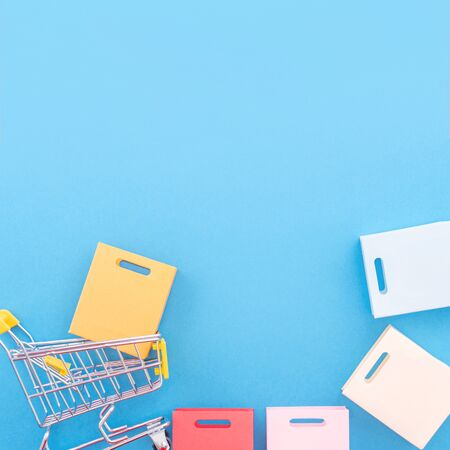 Abstract design element, annual sale, shopping season concept, mini yellow cart with colorful paper bag on pastel blue background, top view, flat lay 免版税图像