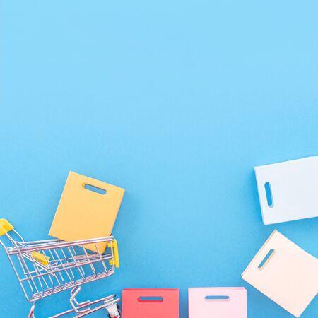 Elemento de diseño abstracto, venta anual, concepto de temporada de compras, mini carro amarillo con bolsa de papel de colores sobre fondo azul pastel, vista superior, endecha plana