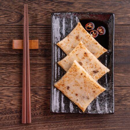Délicieux gâteau de navet, gâteau de radis local traditionnel chinois au restaurant avec sauce soja et baguettes, gros plan, espace de copie, vue de dessus, mise à plat. Banque d'images