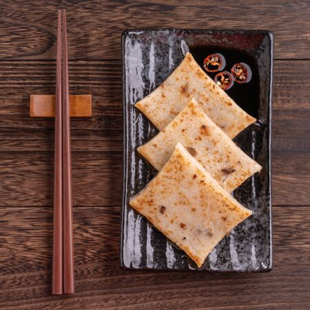 Delicious turnip cake, Chinese traditional local radish cake in restaurant with soy sauce and chopsticks, close up, copy space, top view, flat lay.