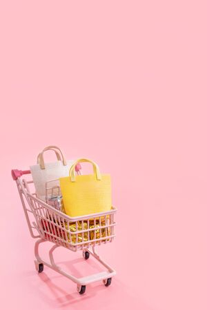 Annual sale shopping season concept - mini pink shop cart trolley full of paper bag gift isolated on pale pink background, blank copy space, close up