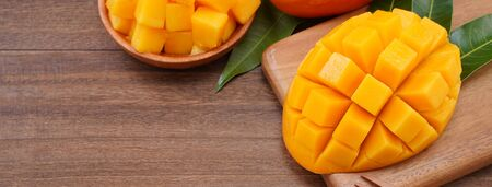 Fresh mango, beautiful chopped fruit with green leaves on dark wooden table background. Tropical fruit design concept. Flat lay. Top view. Copy space 写真素材