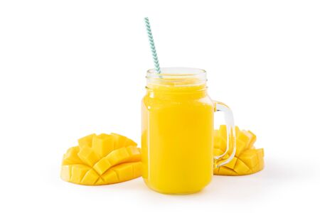 Fresh tropical mango juice with beautiful diced pulp and striped paper straw isolated on white background table, close up, cut out, clipping path.