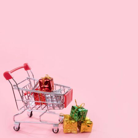 Annual sale, Christmas shopping season concept - mini red shop cart trolley full of gift box isolated on pale pink background, copy space, close up 写真素材