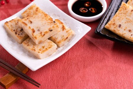 Chinese lunar new year food concept, Delicious turnip radish cake, local cuisine in restaurant with soy sauce on red background,  copy space
