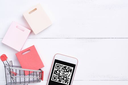 Abstract online shopping,mobile payment with QR code design concept element,colorful cart,paper bag on wooden table background,top view,flat lay