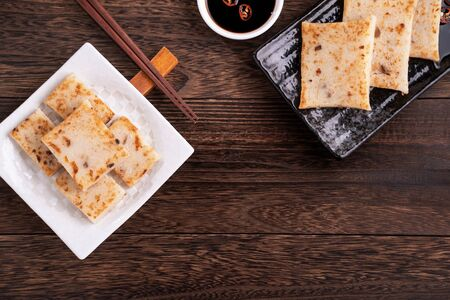 Delicious turnip cake, Chinese traditional radish cake in restaurant with soy sauce for new year's dishes, close up, copy space, top view, flat lay.
