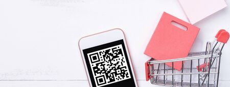 Abstract online shopping, mobile payment with QR code design concept element, colorful cart, paper bag on wooden table background, top view, flat lay