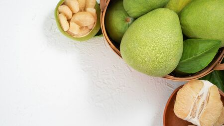 Fresh pomelo, pummelo, grapefruit, shaddock on white cement background in bamboo basket. Autumn seasonal fruit, top view, flat lay, tabletop shot.
