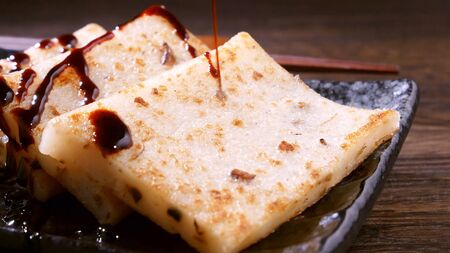 Pouring black soy sauce on ready-to-eat delicious turnip cake, Chinese traditional local dish radish cake in restaurant, close up, copy space.