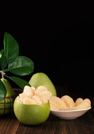 Fresh peeled pomelo, grapefruit, shaddock with green leaves on dark wooden plank table. Seasonal fruit near mid-autumn festival, close up, copy space