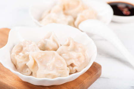 Fresh, delicious boiled pork gyoza dumplings, jiaozi on white background with soy sauce and chopsticks, close up, lifestyle. Homemade design concept.
