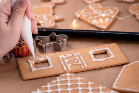 Woman is decorating gingerbread cookies house with white frosting icing cream topping on wooden table background, baking paper in kitchen, close up, macro. Imagens