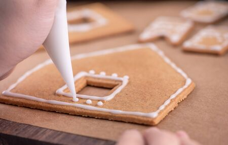 Woman is decorating gingerbread cookies house with white frosting icing cream topping on wooden table background, baking paper in kitchen, close up, macro. Stock Photo