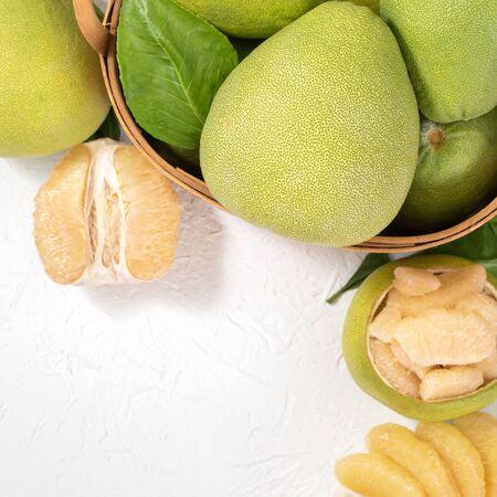 Pomelo frais pelé, pomelo, pamplemousse, shaddock sur fond de bois clair. Fruits de saison d'automne, vue de dessus, mise à plat, photo de table.