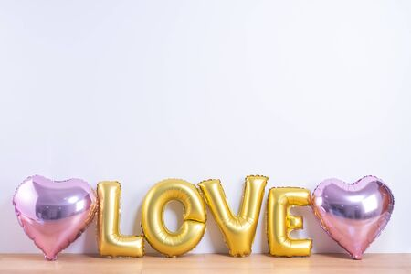 Valentine's day, Mother's day design concept - Beautiful balloon with word love shape on a light wooden floor and white wall background, close up.