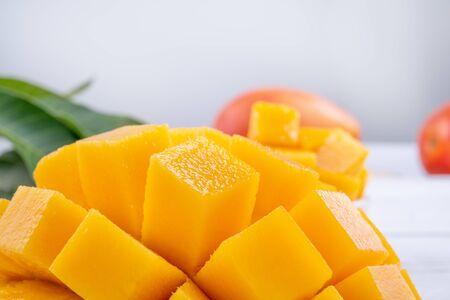 Mango fresco, hermosa fruta picada con hojas verdes sobre fondo de mesa de madera brillante. Concepto de diseño de frutas tropicales, de cerca, copie el espacio. Foto de archivo