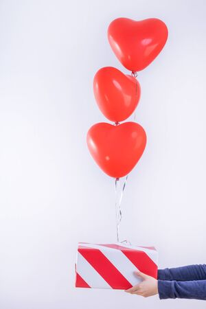 Valentine's day, Mother's day, birthday design concept - Heart helium balloon with gift box on a light wood floor, white wall background, close up.