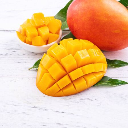 Fresh mango,beautiful chopped fruit with green leaves on bright wooden table background. Tropical fruit design concept, close up, copy space. Foto de archivo