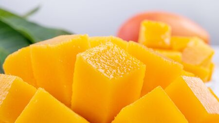 Fresh mango,beautiful chopped fruit with green leaves on bright wooden table background. Tropical fruit design concept, close up, copy space.