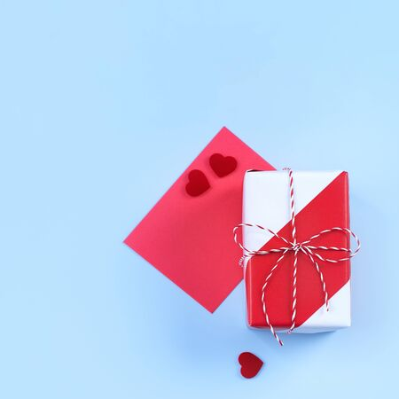 Valentine's Day, Mother's day art design concept for promotion - Red, white wrapped gift box isolated on pastel light blue color background, flat lay, top view.