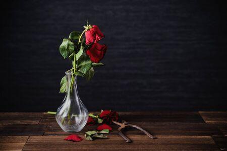 Rose fanée sur fond gris foncé et table en bois avec pétales et feuilles d'automne, concept de design de la triste romance de la Saint-Valentin, brisée, copie, espace. Banque d'images