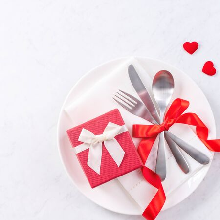 Valentine's Day, Mother's Day, holiday dating meal, banquet design concept - White plate and red ribbon on marble background, top view, flat lay.