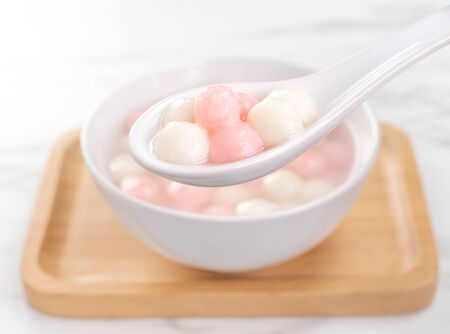 Delicious tang yuan, red and white rice dumpling balls in a small bowl. Asian traditional festive food for Chinese Winter Solstice Festival, close up.