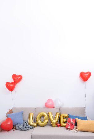 铝箔爱情气球和礼物在沙发上与白色墙壁的背景为情人节,母亲节惊喜的设计理念。