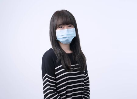 Young Asian woman portrait, wearing a medical surgical blue face mask to prevent infection sick, air pollution isolated on white background, copy space, close up, cut out