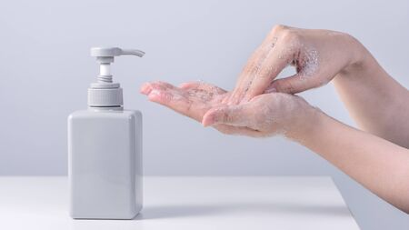 Washing hand. Asian young woman using liquid soap to wash hands, concept of hygiene to stop spreading coronavirus isolated on gray white background, close up.