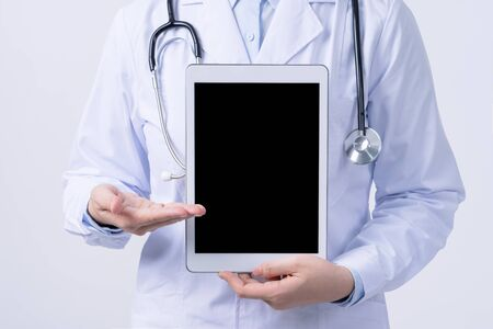 Doctor with stethoscope in white coat holding tablet, showing medical information, diagnosis, isolated on white background, close up, cropped view.