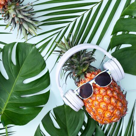 Funny pineapple wearing white headphone, concept of listening music, isolated on blue background with tropical palm leaves, top view, flat lay design.