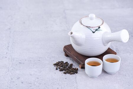 Hot tea in white teapot and cups on a sieve over bright gray cement background, closeup, copy space design concept. Stock Photo