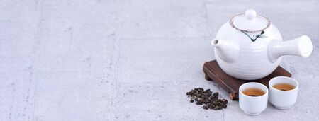 Hot tea in white teapot and cups on a sieve over bright gray cement background, closeup, copy space design concept.