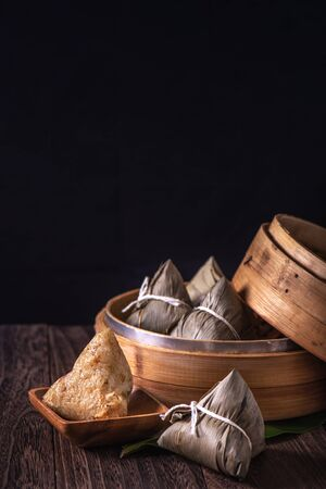 Zongzi - Chinese rice dumpling zongzi in a steamer on wooden table black retro background for Dragon Boat Festival celebration, close up, copy space.