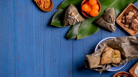 Rice dumpling, zongzi - Traditional Chinese food on blue wooden background of Dragon Boat Festival, Duanwu Festival, top view, flat lay design concept.