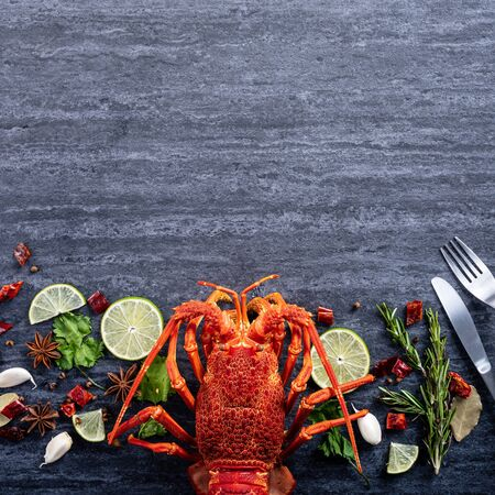Cooked boiled lobster, delicious dinner seafood meal set with knife and fork on black stone slate background, restaurant menu design, top view, overhead