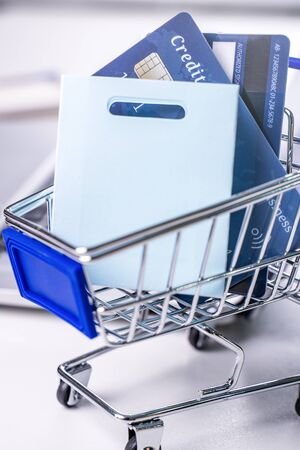 Office online paying, stay home shopping, electronic payment with credit card concept, laptop on white table background with shop cart, close up. Фото со стока