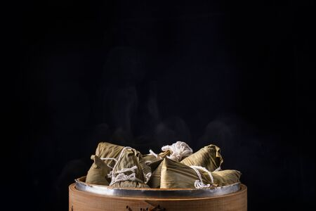 Rice dumpling, zongzi - Bunch of Chinese traditional cooked food on wooden table over black background, concept of Dragon Boat Festival, close up, copy space