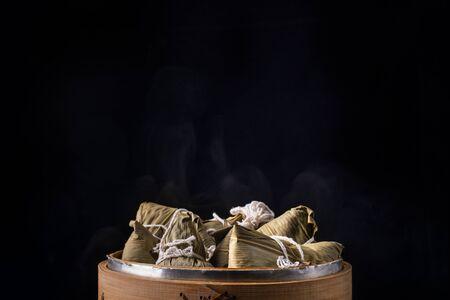 粽子、粽子——一串中国传统熟食放在木桌上,以黑色为背景,概念端午节,拉近,复制空间