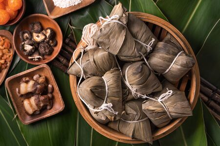 Rice dumpling, zongzi - Traditional Chinese food on green leaf background of Dragon Boat Festival, Duanwu Festival, top view, flat lay design concept.