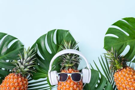 Funny pineapple wearing white headphone, concept of listening music, isolated on colored background with tropical palm leaves, top view, flat lay design.